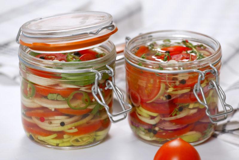 Половинки томатов в зимней заготовке с петрушкой и чесноком